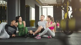Group of sporty people sitting on floor at gym. Group of young sporty smiling people sitting on floor, talking after workout, friends having rest before fitness Royalty Free Stock Photography