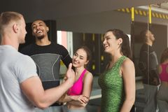 Group of sporty people talking at gym. Group of young sporty smiling multiethnic people having fun, talking after workout, friends having rest before fitness Royalty Free Stock Image