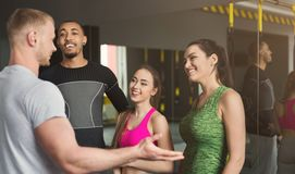 Group of sporty people talking at gym. Group of young sporty smiling multiethnic people having fun, talking after workout, friends having rest before fitness Stock Photos
