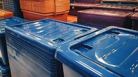 Group of Stacked Plastic Boxes with Lids at Store. Group of Stacked Orange, Blue, and Brown Plastic Boxes with Lids at Store stock photo