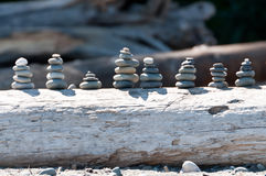 Group of stacked rocks on driftwood Stock Images