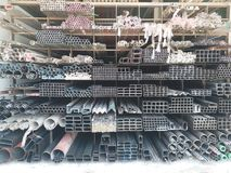 Group of steel profile storaged in different shapes such bar,square,tube and pile display on store. Group of steel profile storaged in different shapes such bar Royalty Free Stock Photography