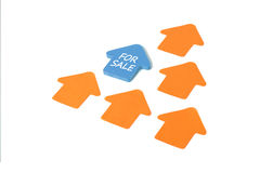 House for sale post-it. A group of stickers shaped like house on white background. For sale is written on one of them Royalty Free Stock Photos