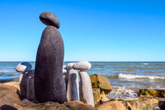 Group of stones. Black stone confront to group of the white stones Stock Photo