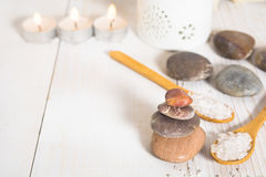 Group of stones with sea salt on the spoons and line of candles Stock Images