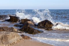 Group of stones on the shore and splashes from the waves. A group of stones on the shore and splashes from the waves. Black sea seascape Stock Image