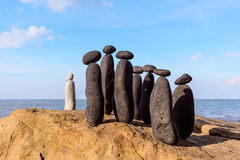 Group of stones. White stone confront to black group on the seashore Royalty Free Stock Photography