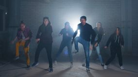 Group of street dancers performing different moves on the dark street.
