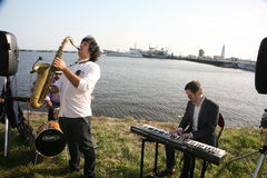 Group of street musicians in the background of the Gulf of Finland in the civil port of Kronstadt. Speech after a concert Opera at the final meeting, after royalty free stock photos
