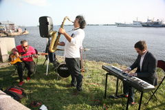 Group of street musicians in the background of the Gulf of Finland in the civil port of Kronstadt. Speech after a concert Opera at the final meeting, after royalty free stock image