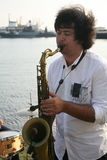 Group of street musicians in the background of the Gulf of Finland in the civil port of Kronstadt. Stock Photos