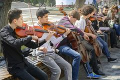 Group of street musicians playing the violins and the cello royalty free stock photography