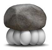 Group Strength Organization. Business concept with a rock or boulder being lifted and supported by a team of white eggs working together to create a strong Royalty Free Stock Photos