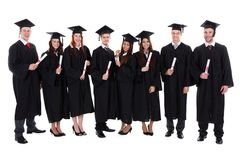 Group of student graduates with their diplomas. Group of diverse student graduates with their diplomas in their hands wearing gowns and mortar boards standing in Royalty Free Stock Image