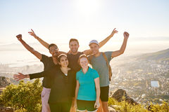 Group of student hikers posing on a mountain nature trail. Happy group of student hikers smiling joyfully and posing together while hiking a nature trail on a Stock Photo
