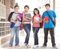 Group student holding books and standing at school Stock Image