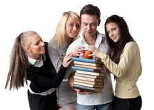 Group of students. Male student with books and an apple among beautiful female students Royalty Free Stock Photos