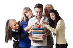 Group of students. Male student with books and an apple among beautiful female students Stock Photos