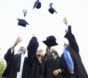 Group Of Students Attending Graduation Ceremony throwing Mortar Boards In The Air Stock Photos