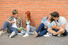 Group of students with books hanging out Royalty Free Stock Photos