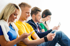 Group of students on a break. Focus on a boy using smartphone Stock Photography
