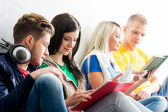 Group of students on a break. Focus on a girl reading a textbook. Background is blurry Stock Images