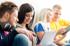 Group of students on a break. Focus on a girl using tablet. Background is blurry Royalty Free Stock Images
