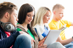 Group of students on a break. Focus on a girl using tablet. Background is blurry Stock Photos