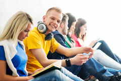 Group of students on a break. Focus on a girl using tablet. Background is blurry Stock Image