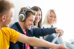 Group of students on a break. Focus on a girl using tablet. Background is blurry Stock Photo