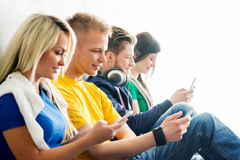 Group of students on a break. Focus on a girl using tablet. Background is blurry Royalty Free Stock Image