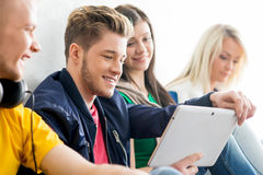 Group of students on a break. Focus on a happy boy using tablet. Background is blurry Stock Photo