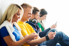 Group of students on a break. Focus on a happy boy using tablet. Background is blurry Royalty Free Stock Photography