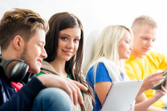 Group of students on a break. Focus on a happy boy using tablet. Background is blurry Stock Image