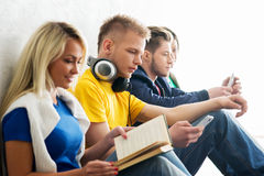 Group of students on a break reading books and using smartphones. Focus on a boy in headphones. Background is blurry Royalty Free Stock Photos