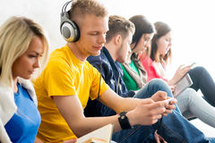Group of students on a break reading books. And using smartphones. Focus on teenage boy. Background is blurry Royalty Free Stock Photos