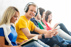 Group of students on a break reading books and using smartphones. Focus on a teenage boy. Background is blurry Royalty Free Stock Photography