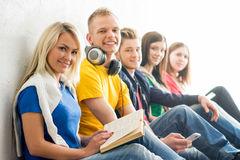Group of students on a break reading books. And using smartphones. Focus on a teenage boy and girl. Background is blurry Royalty Free Stock Photography