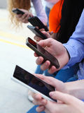 Group of a students chatting with their smartphones. At the park. Close up royalty free stock images