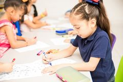 Group of students coloring in class. Portrait of a little girl doing a coloring activity with the rest of the group in a preschool classroom royalty free stock photos