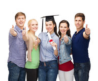 Group of students with diploma showing thumbs up Stock Images