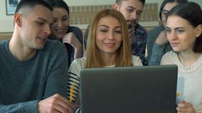 Group of students discusses something on laptop. Group of caucasian students disscussing something on laptop at the college. Brunette bearded guy sitting on the Royalty Free Stock Image