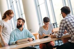 Group of students discussing in university library. Group of young students discussing in university library royalty free stock image