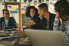 Group of students eating pizza at college canteen royalty free stock image