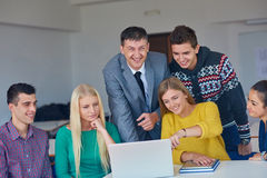 Group of students getting suppport from teacher Stock Images
