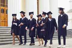 Group of students graduates go against the university college. Group of students graduates go smiling against the background of university college. Graduation stock photos