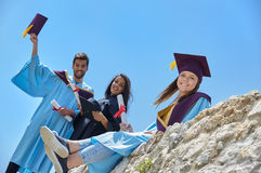 Group of students in graduation gowns and caps Royalty Free Stock Image