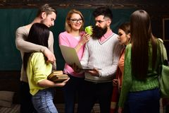 Group of students, groupmates spend time with teacher, lecturer, professor. Students, scientists studying after classes. Professor holds laptop, teaches royalty free stock photo