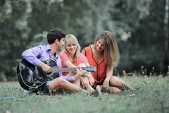 Group of students with a guitar relax sitting on the grass in the city Park.  royalty free stock photos