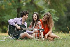 Group of students with a guitar relax sitting on the grass in the city Park.  stock photos